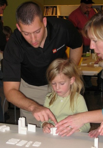 Adam Reed Tucker works with a child at a seminar to show the many uses of the LEGO brick.