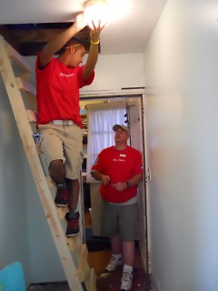 Two Lowe's employees work to put in a new, energy efficient lightbulb, using the new step ladder.