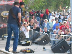 Band leader Wayne Baker Brooks leading his band group and singing before large crowd of concert goers.
