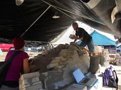 Wozniak and friend, Adena Koslek, debate the best location for fresh kiln bricks.