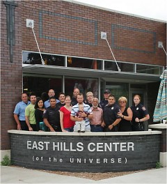 """Members of East Hills Council of Neighbors photographed in front of the """"Center of the Universe"""" building"""