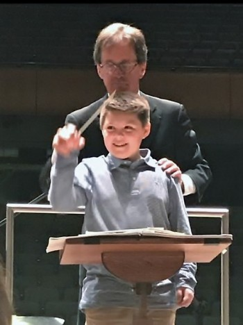Emmet Claypool, age 10, conducts the Grand Rapids Symphony, assisted by John Varineau.