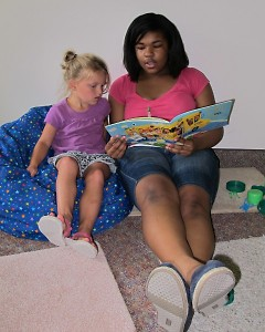A teen volunteer reads with a child