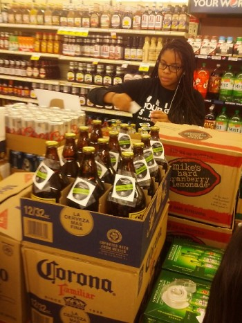 A volunteer works diligently to place stickers on alcoholic beverages