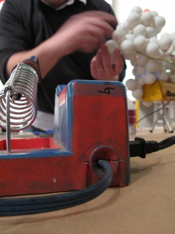 Sam Blanchard puts the finishing touches on his ping pong chandelier, which mimics lightening patterns.