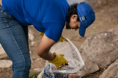 A volunteer picks up trash along the Grand River at last year's Mayors' Grand River Cleanup