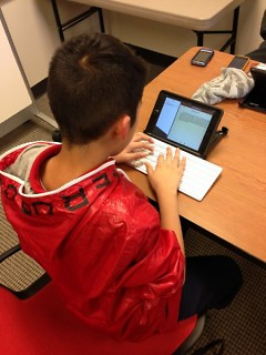 a Press Club member uses an iPad to write his story for The Rapidian