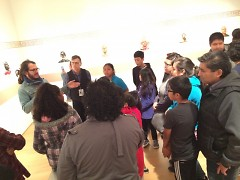 Students and families gather around Salvador Jimenez Flores as he talks about his Artprize entry at the GRAM