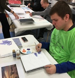 Reed working with paint during a free art session