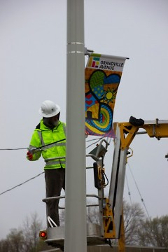 Bill Moerdyk of Habitat Kent installs the banners that will be displayed on light posts down Grandville Ave south of Wealthy St
