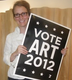 Amelea Pegman poses with ArtPrize 2012 sign, available to purchase for 5 dollars.