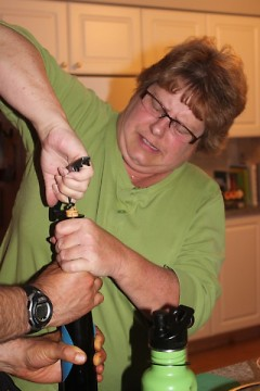 Griffins Booster Club president Jill DeWitt opens celebratory wine bottle
