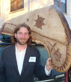 Kevin Finney stands by an authentic Ojibwe-style birch-bark canoe built last year by 50 fifth graders.