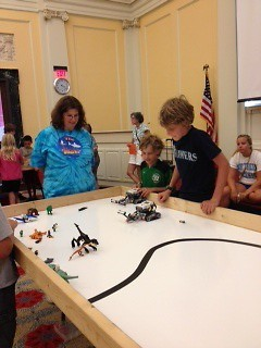 Tami Hartley watches as robots attempt to rescue mini-figs from dinosaurs