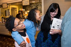 Student authors and a volunteer celebrate in the Wealthy Theatre lobby