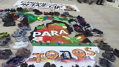 "The Michigan Map bears the words ""Licensias Para Todos"" and is surrounded by the walkers' shoes, representing their journey."