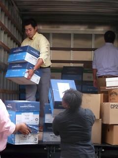 Varnum employees help to unload a truck full of school supplies at Buchanan Elementary.