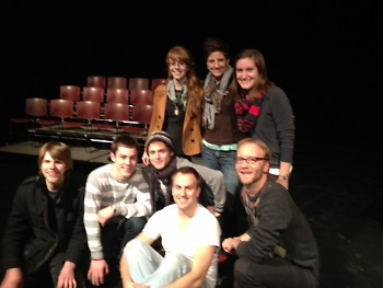 Seven of the play's ten cast members pause for a group shot during rehearsal.