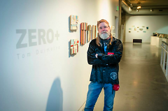Tom Duimstra poses with his work displayed at UICA