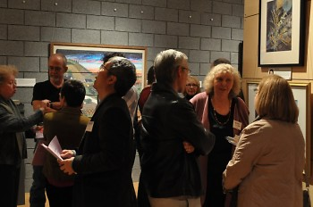 Artists and community members mingle together admiring the exhibits.