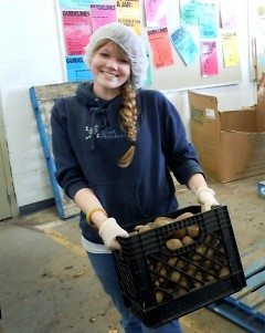 Rachel Rounds hefts one of many boxes of potatoes she and her friends sorted on Valentine's Day.