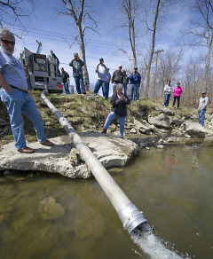 Here, year-old Steelhead Salmon are being stocked in the Huron River at Rockwood.