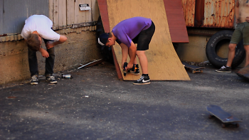 Still of skateboarders constructing a skating structure