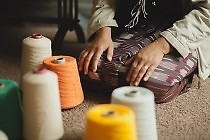 That Wah, a Burmese refugee resettled by BRS, hand weaves scarves, bags and scarves.