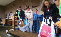 Feeding America West Michigan staff and volunteers unload food at the Kentwood Post Office branch in 2016.