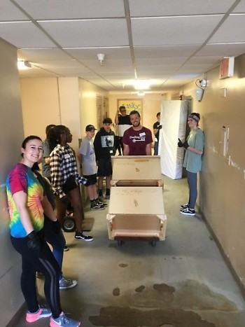 Volunteers from Bike and Build clean out Ferguson Apartments during Property Days so the building can undergo renovations.