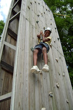 Camp O'Malley camper attempting to conquer the camp's climbing wall, one of the many fun, outdoor activities available!