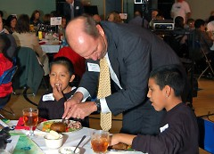 A sponsor helping the Club members at his table cut up their delicious steak dinners.